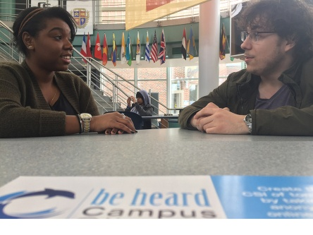 CSI students in the campus center, sitting across from adverts left in the cafeteria (Photo Credit: Clifford Michel)