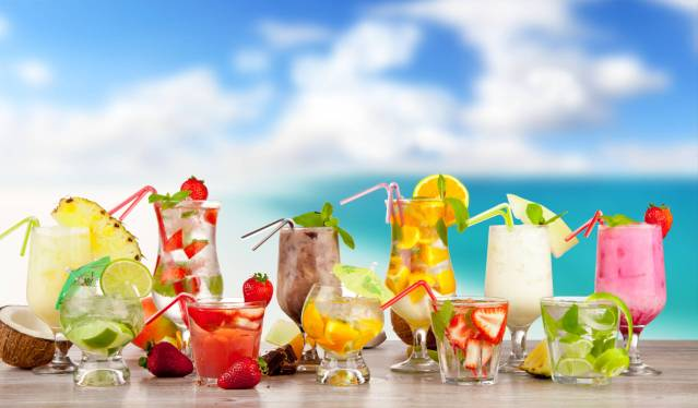 Summer cocktails with pieces of fruit on wooden table. Blur beach on background